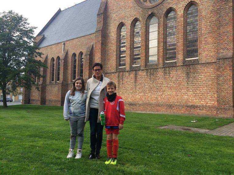 Fien Ingelbrecht (9), Heidi Devreker en Louis Dekeyser (8) aan de achterzijde van de kerk, waar de glijbaan zal uitgeven op het buitenspeelplein.