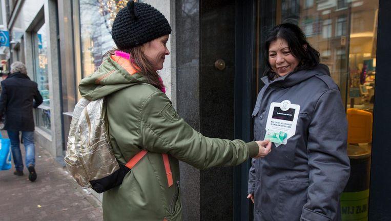 De dakloze Carla ontvangt een euro via haar pinjas. Beeld Dingena Mol