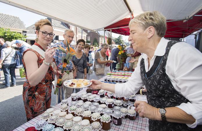 Jamkoningin Mireille ter Haar proeft een cracker met jam in een kraam op de Borculoseweg tijdens de jammarkt.