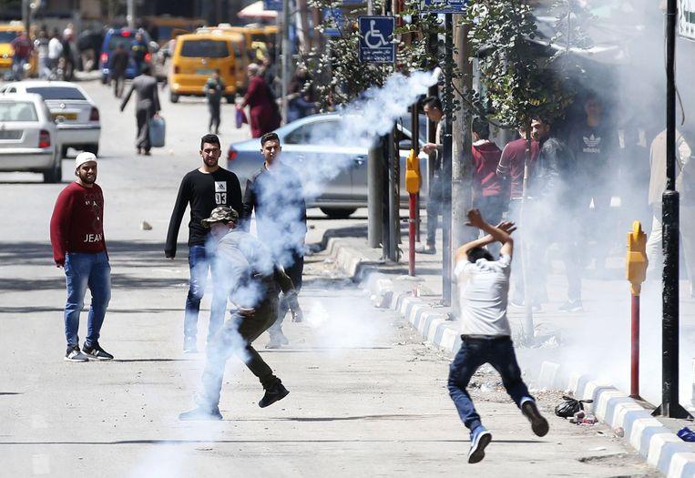 Palestijnse demonstranten in de stad Hebron op de Westelijke Jordaanoever zoeken dekking na waarschuwingsschoten van het Israëlische leger. Beeld AFP