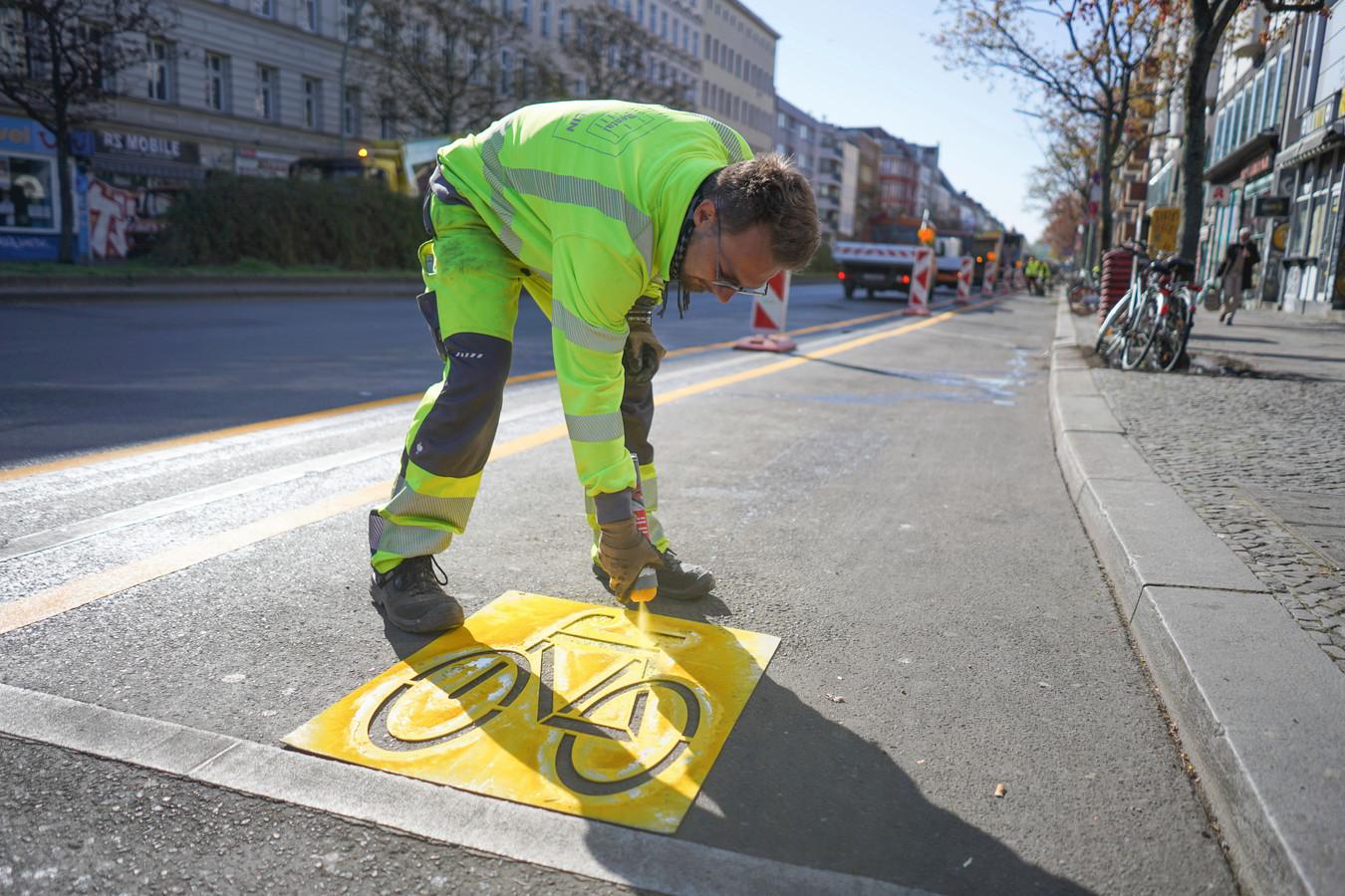 Stadsmedewerker brengt markeringen aan op een tijdelijk fietspad in Berlijn.