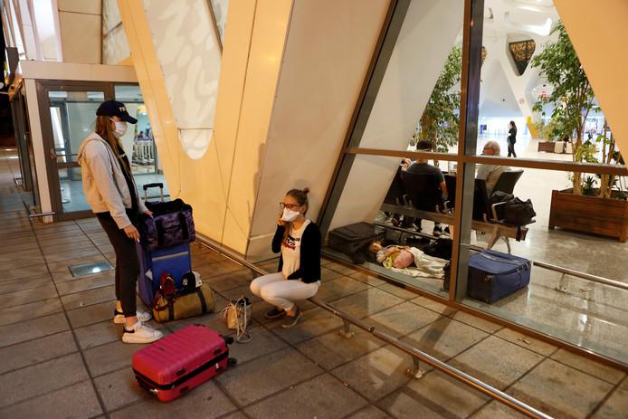 Toeristen wachten op het vliegveld van Marrakech in Marokko op repatriëring.