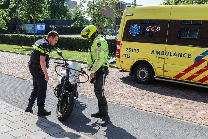 Politie-agenten inspecteren de motor nadat een bestuurster er tijdens een motorrijles een ongeval mee heeft gehad.