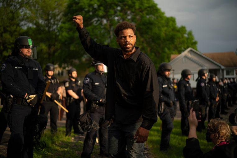 Een betoger loopt maandag in Oakdale, Minnesota langs de politie die de woning van de ontslagen politieagent Derek Chauvin bewaakt. Chauvin is de agent die George Floyd doodde door langdurig zijn knie in zijn nek te duwen. Beeld AP