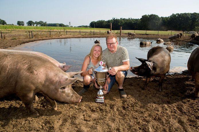 Melissa Schuurman en Koen Lipman met de beker, te midden van hun varkens.