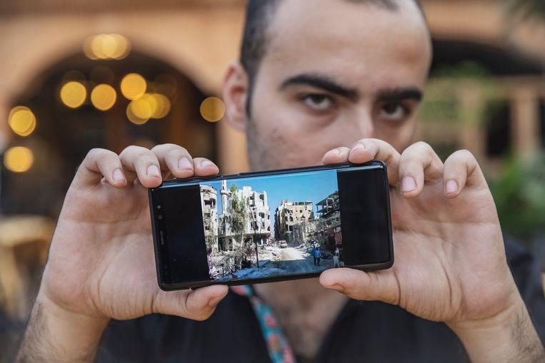 Khaled laat op zijn mobiele telefoon foto's en video's zien van de ravage die de oorlog heeft aangericht in zijn geboortestad. Beeld Sven Torfinn