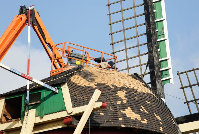 Molenmaker Jan Vaassen repareert het dak van eiken schaliën.