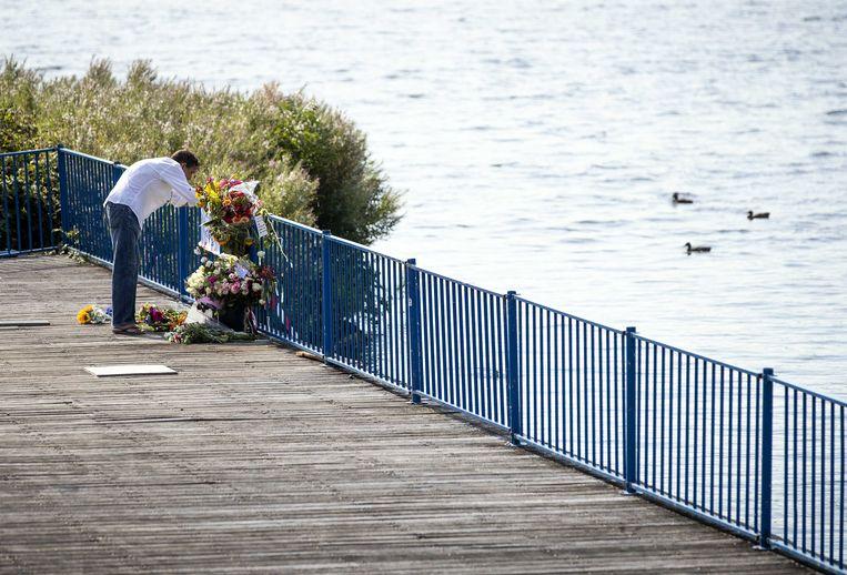 Bloemen op de plek waar Bas van Wijk werd doodgeschoten. De 24-jarige man werd neergeschoten bij de Amsterdamse recreatieplas de Oeverlanden. Beeld ANP