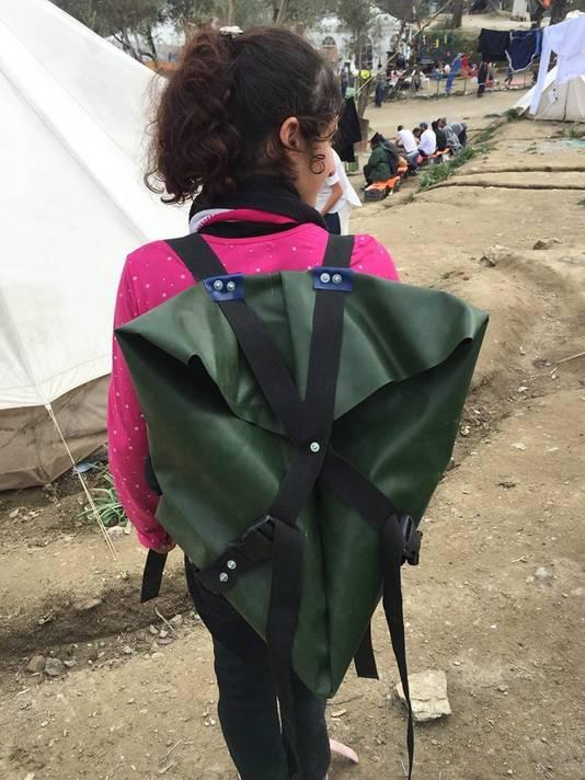 Een jonge vluchtelinge met haar eigen rugtas gemaakt van rubberboten en reddingsvesten.