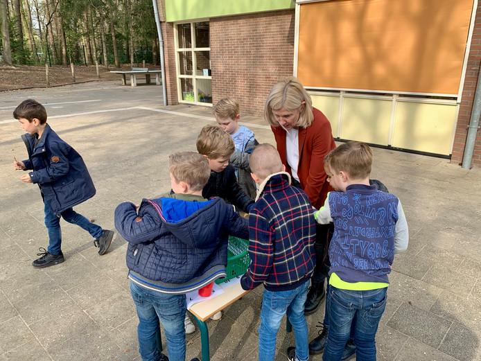 Juf Margreet helpt de kinderen bij de rekenles op het schoolplein.