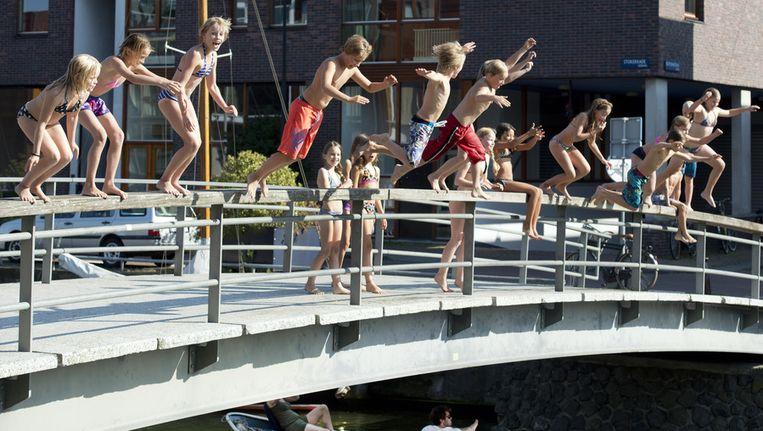 Kinderen springen van een brug aan de Stokerkade in Amsterdam afgelopen vrijdag, op de eerste tropische septemberdag sinds 1949. Beeld anp