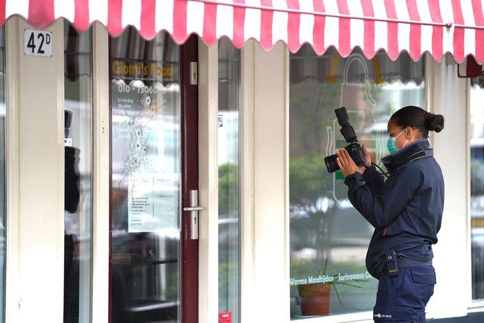 Een rechercheur van de forensische opsporing legt de kogelgaten in de deur van het eethuis aan de Frits Ruysstraat vast op beeld.