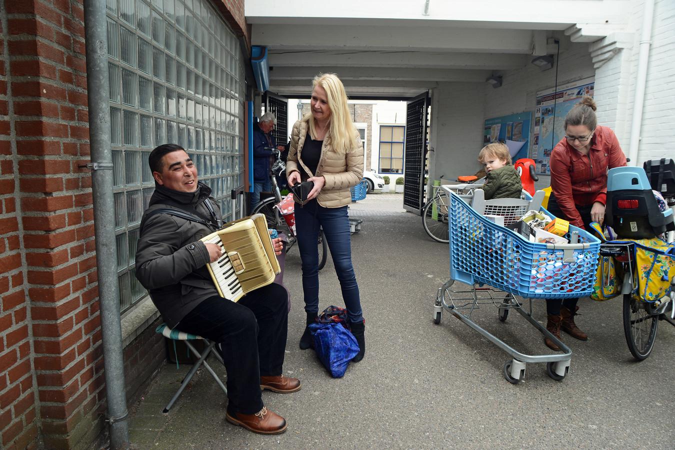 Marin Vasilev is al 16 jaar een vertrouwd gezicht in de passage bij de AH-supermarkt in Zierikzee. Irene Gijlstra beloont zijn spel op de geleende accordeon met een euro in zijn mandje.