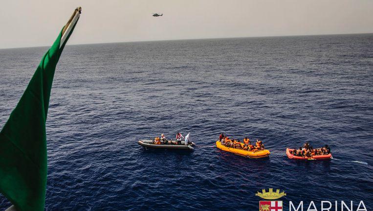 Foto van de Italiaanse kustwacht die boten met migranten oppikt voor de Libische kust.