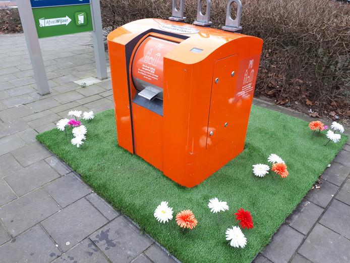 Kunstgras en bloemen sieren de ondergrondse container aan het Titus Brandsmaplein.