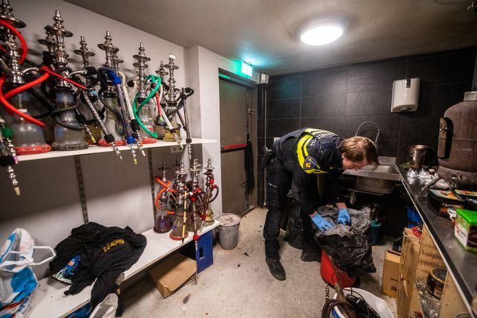 Onderzoek in een waterpijpcafé aan de Alphense Van Nesstraat. Volgens de politie werd die gebruikt om drugsgeld wit te wassen.