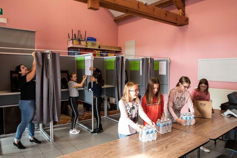 De kinderen van basisschooltje 'Tumuli' helpen met de details van het stembureau.