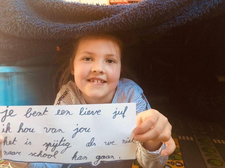De kinderen toonden juf Dinah boodschappen van achter het raam.