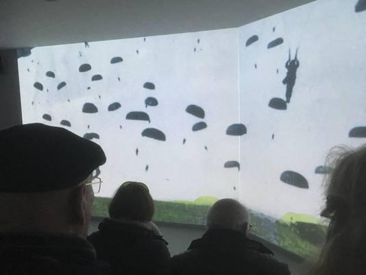 Bezoekers van Infocentrum WO2 in Nijmegen kijken in filmzaal De Experience naar de landing van parachutisten.