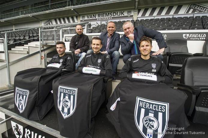 De Heracles-spelers Thomas Bruns, Bram Castro en Mark-Jan Fledderus testen de dug-outteddy. Op de achtergrond zitten vanaf links Marcel Schorn van Erma Sport, Heracles-directeur Nico-Jan Hoogma en bedenker Marcel Willemsen.