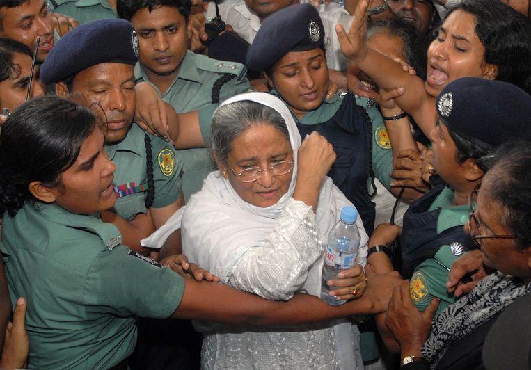 Politieagenten escorteren opositieleidster en oud-premier van Bangladesh Sheikh Hasina maandag naar de rechtbank. Zij is aangehouden en wordt beschuldigd van moord, corruptie en het in gevaar brengen van de staat. (AP) Beeld null