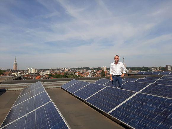 Schepen David Dessers tussen de zonnepanelen op het Leuvense stadskantoor.