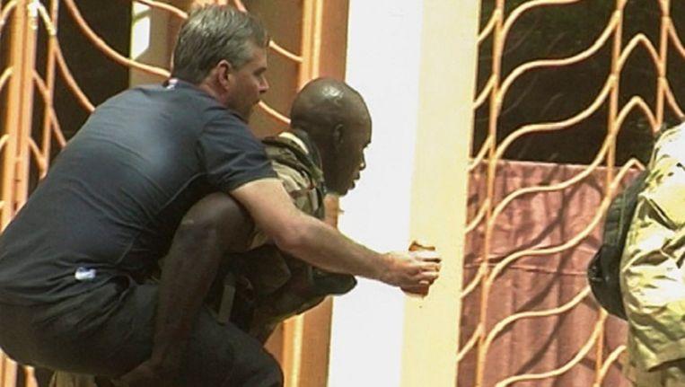 Een soldaat helpt een gewonde gijzelaar.
