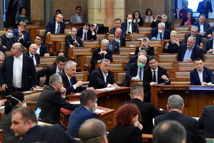Met de maandag in het parlement aangenomen wet kan Viktor Orbán (midden) grotendeels per decreet regeren