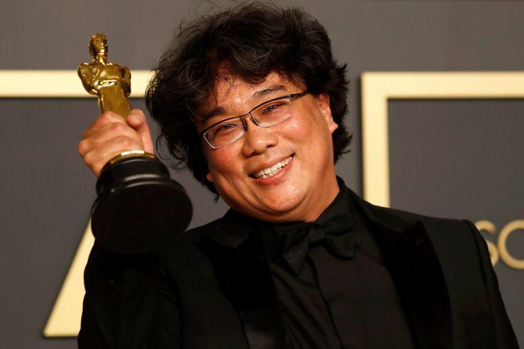 Bong Joon-ho met een van van de vier Oscars die zijn film, Parasite, zondagnacht won. In eigen land is hij een held geworden. Beeld EPA