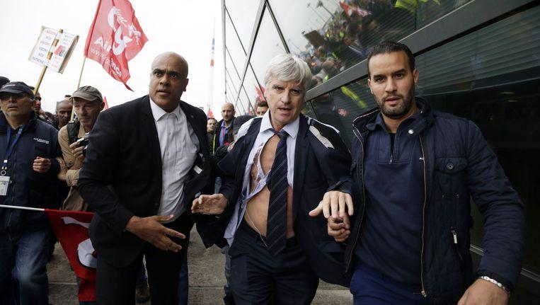 Directeur Pierre Plissonnier wordt weggevoerd door beveiliging nadat hij is belaagd door boze werknemers Beeld afp