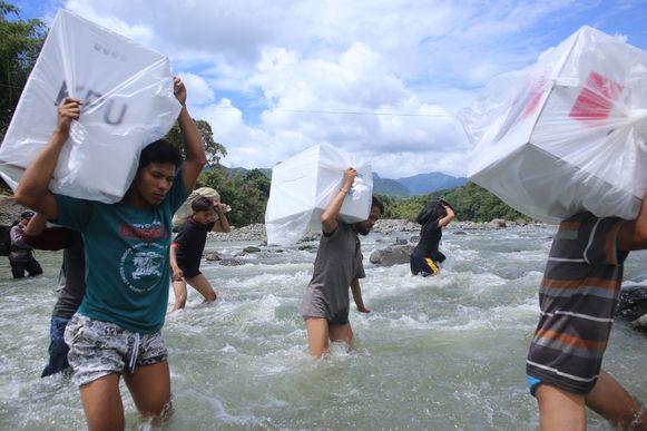 Indonesische verkiezingsmedewerkers dragen stembussen door een rivier naar een afgelegen dorpje in het zuiden van Sulawesi.