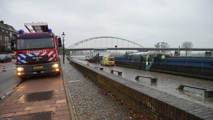 Het binnenvaartschip waar het slachtoffer afgelopen nacht naar beneden viel en gewond raakte. Hulpdiensten halen hem eruit.