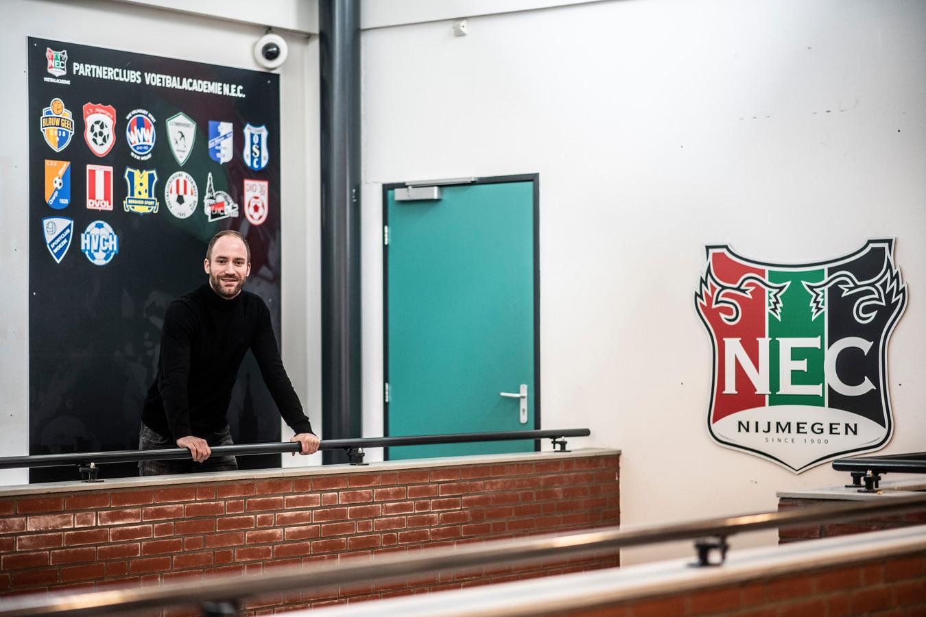 Hoofd jeugdscouting Dominique Scholten van NEC met achter hem het bord met logo's van amateurclubs waarmee NEC samenwerkt en een partnerschap sloot.