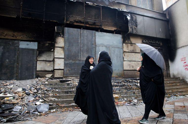 Iraanse vrouwen kijken naar een bankfiliaal dat veel schade leed tijdens onlusten in Iran, die onstonden toen mensen de straat opgingen om te protesteren tegen stijgende benzineprijzen.  Beeld EPA