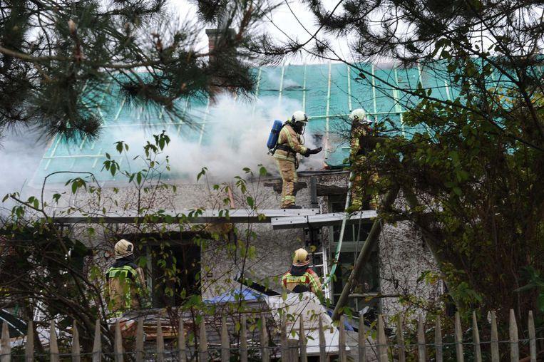 De brandweer gaat de uitslaande brand te lijf.
