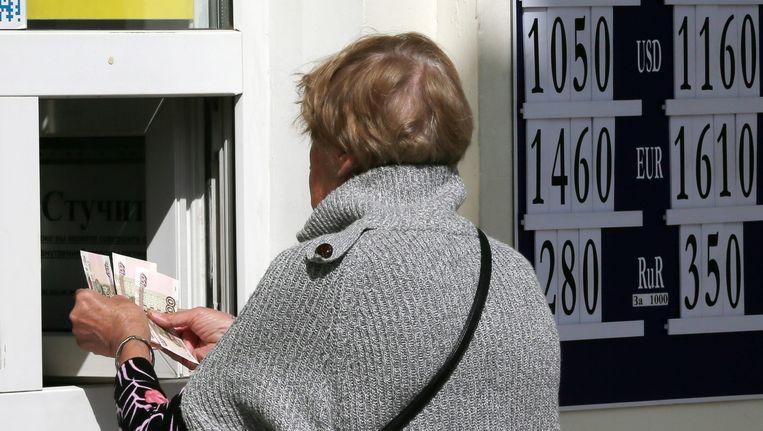 Een vrouw die haar Russische roebels in ontvangst neemt bij een wisselkantoor op de Krim. Beeld epa