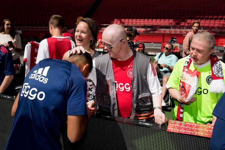 Justin Kluivert deelt handtekeningen aan een fan uit. Beeld ANP