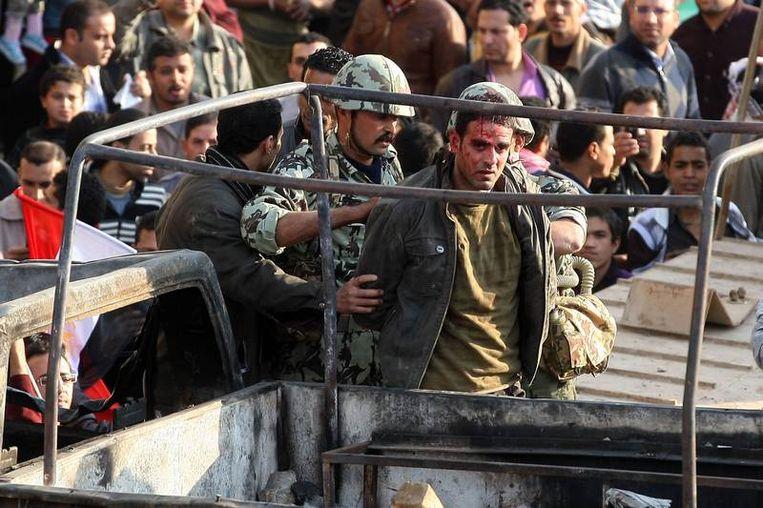 Egyptische militairen arresteren een gewonde anti-Mubarakdemonstrant. Beeld afp