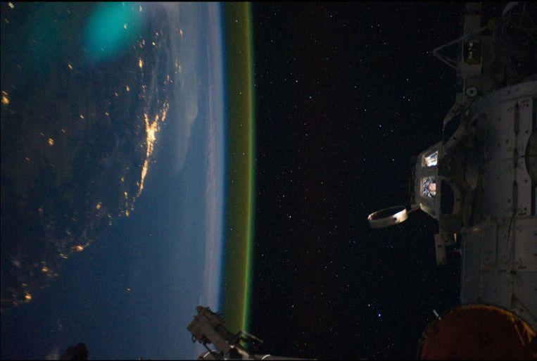 De Cupola, het observatieonderdeel van het Internationaal Ruimtestation (ISS), met een blik op de bemanning en met stadslichten van de aarde op de achtergrond. De stad Brisbane in Australië is goed te zien. Beeld NASA