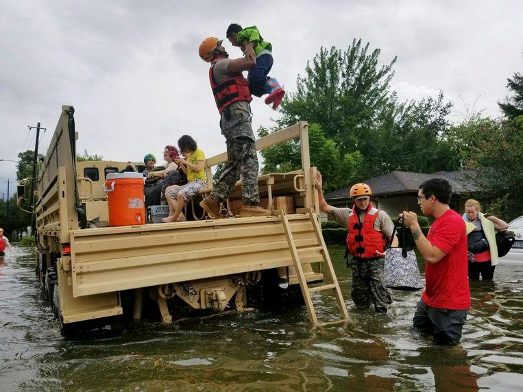 Militairen van de Texaanse Nationale Garde helpen mensen in ondergelopen buurten in Houston, Texas. Zo'n 3000 reservisten zijn opgeroepen om de reddingsdiensten bij te staan. Beeld EPA