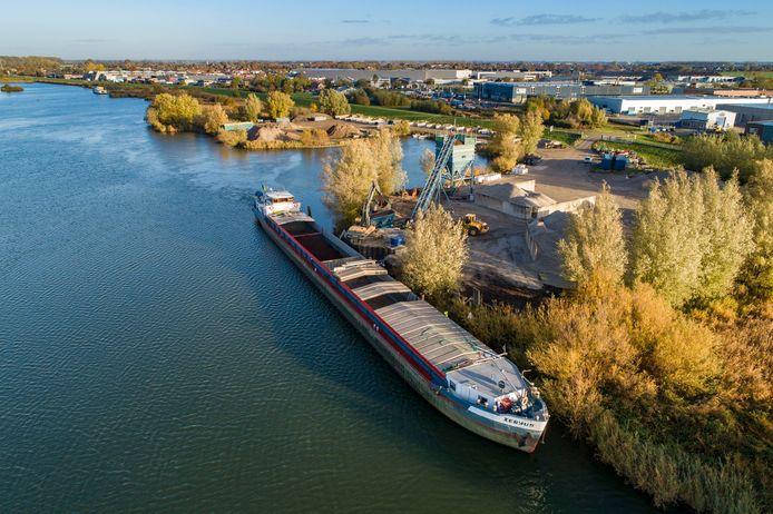 Een binnenvaartschip wordt bij het Kamper bedrijf Stoter geladen voor transport. Het schip wordt maar voor de helft gevuld, vanwege de lage waterstand.