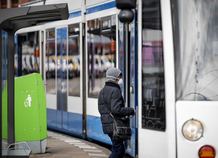 Een passagier stapt de tram in op Amsterdam Centraal. Beeld ANP