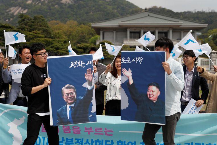 Studenten houden foto's vast van de Noord-Koreaanse leider Kim Jong-un en de Zuid-Koreaanse president Moon Jae-in tijdens een demonstratie voor de hereniging van Noord- en Zuid-Korea in Seoul. Beeld REUTERS