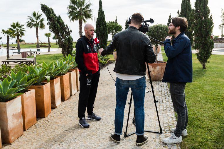 Medewerkers van AT5 praten met Ajax-trainer Erik ten Hag tijdens een trainingskamp. Beeld ANP