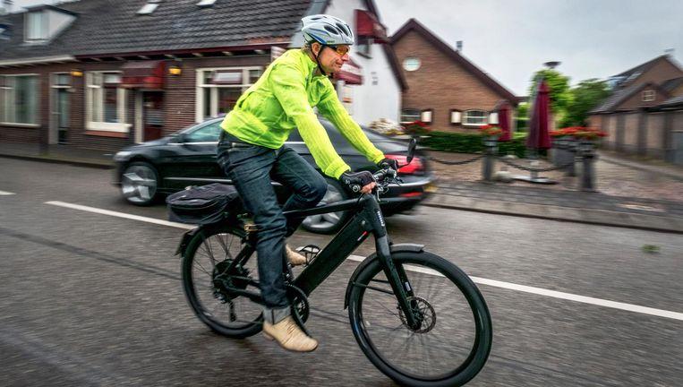 Huisarts Han Rademaker op zijn speedpedelec op de rijbaan in Hoogland. Beeld Raymond Rutting / de Volkskrant