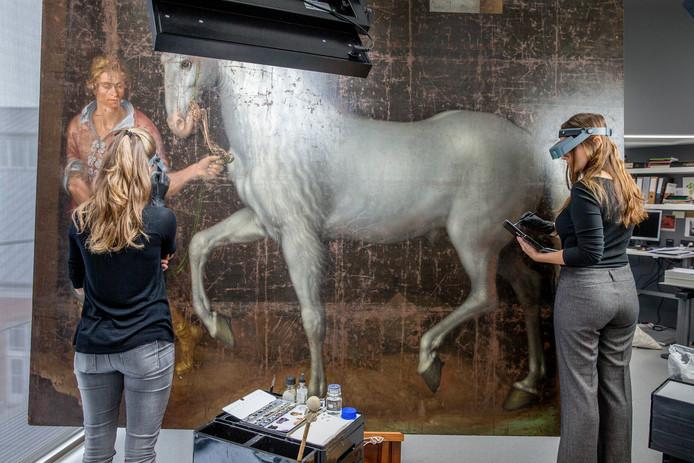 Anneliese Földes (links) en Jorinde Koenen restaureren De Spaanse strijdhengst. Het werk lag lange tijd als A3'tje opgevouwen. Het paard op het schilderij van Jacob de Gheyn is een oorlogsbuit, vandaar dat het zo groot is afgebeeld. Met deze trofee moest worden gepronkt.