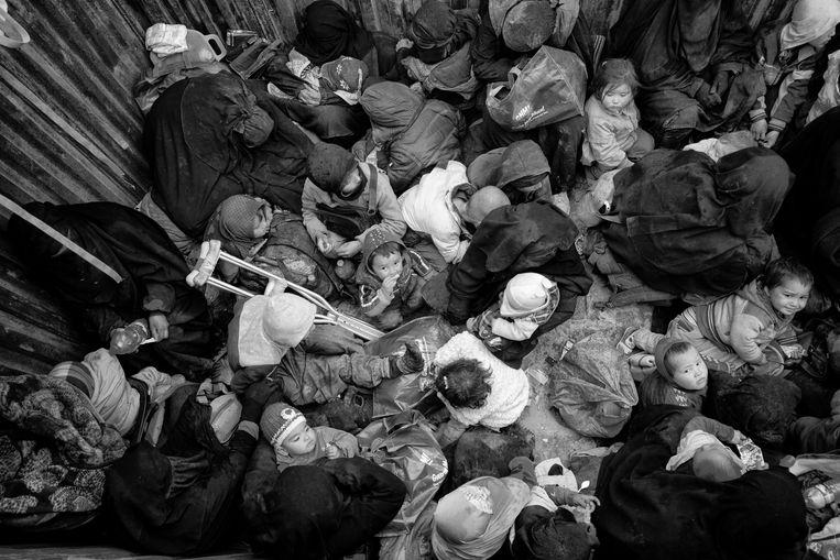 IS families, totale chaos in de trucks, met veelal de vrouwen en de jonge kinderen, ze worden in de laadbakken van trucks naar Al Hol Kamp vervoerd, een tocht van vele uren, na lange tijd hebben ze pinda's te eten gekregen. Beeld Eddy van Wessel