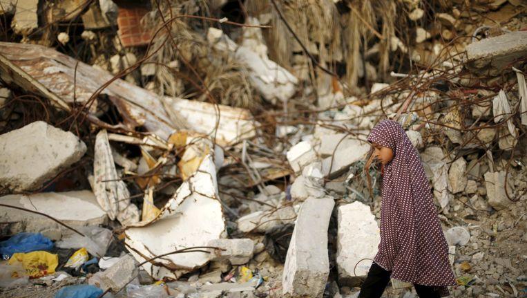 Een Palestijns meisje loopt langs een verwoest huis, dat volgens getuigen is gebombardeerd door Israël tijdens de 50-dagen durende oorlog vorig jaar. Beeld reuters