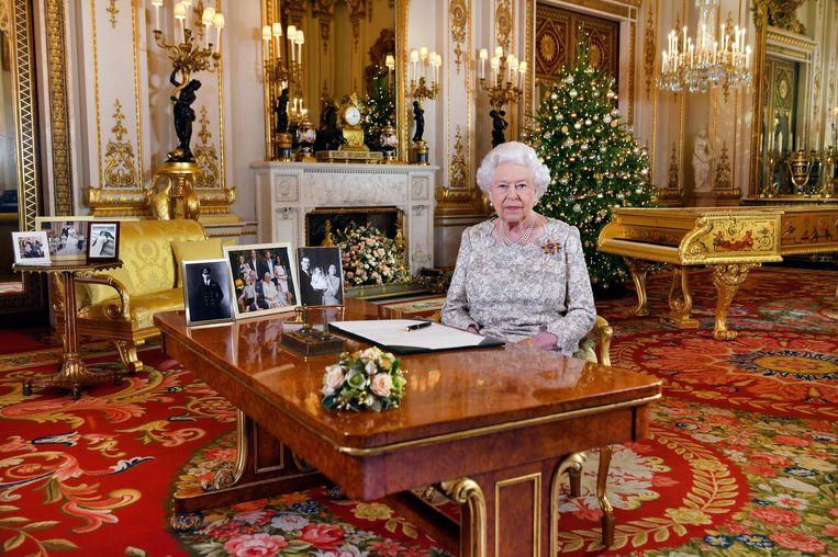 Photo News | De kerstspeech van Queen Elizabeth II werd al op 12 december opgenomen in Buckingham Palace. Rechts staat de gouden piano. Op de haard een gouden klok.