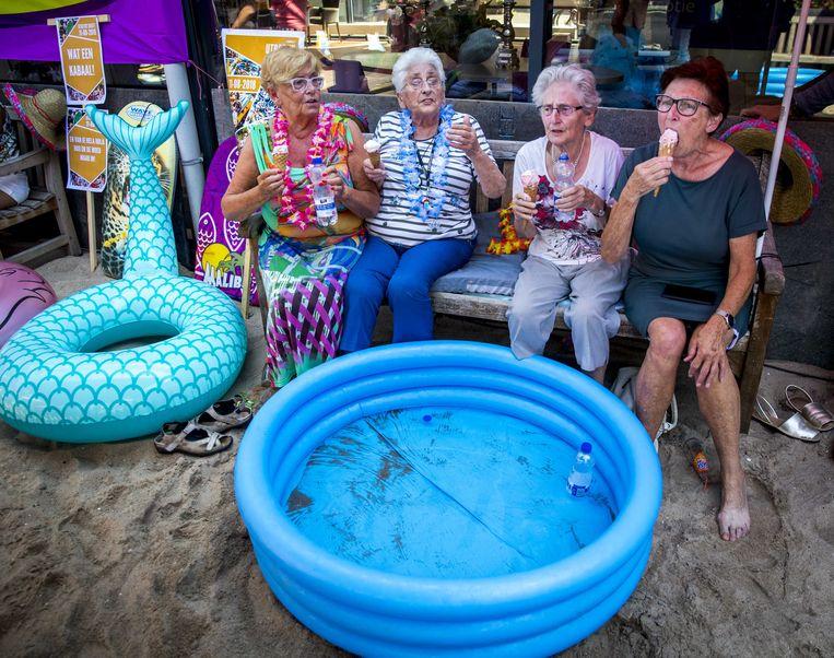 Ouderen van een zorgcentrum in het Rotterdamse Crooswijk genieten van het zomerse weer. Om de bewoners vanwege de aanhoudende hitte wat verkoeling te geven hebben ze een strandje aangelegd. Beeld ANP